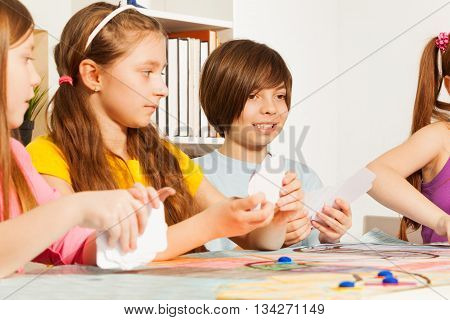 Four kids, friends, playing blanked cards for a pastime