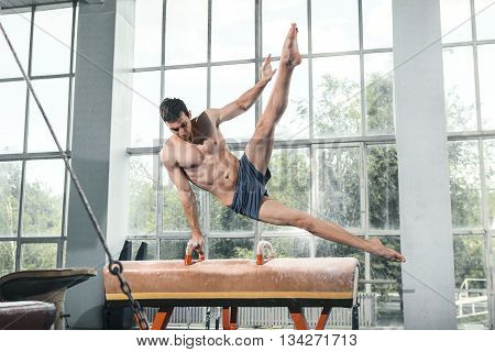 The sportsman the guy performing difficult exercise, sports gymnastics