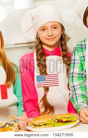 Beautiful young cook, girl in apron and cook hat with American flag and hamburgers on the plate