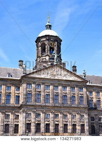 City hall or town hall of Amsterdam, the Netherlands. Historic building facade with bell tower and blue sky.