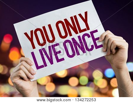 You Only Live Once placard with night lights on background