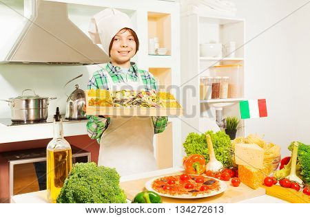 Young cook, boy in apron an hat, holding tray with mix of Italian pasta in the kitchen