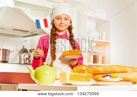 Young French baker, girl in white apron and cap with fresh bakery food in the kitchen