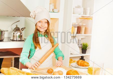 Smiling girl in white apron and cook hat making bakery dough, holding wooden rolling pin in the kitchen