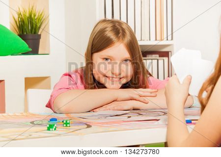 Happy  ten years old girl, little winner, having rest after playing cards with her opponent
