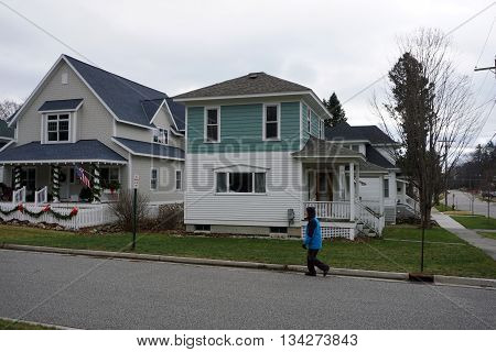 HARBOR SPRINGS, MICHIGAN / UNITED STATES - DECEMBER 24, 2015: A pedestrian walks past homes on Fourth Street in Harbor Springs during Christmas Eve.