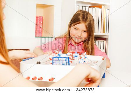 Two girls having fun playing table board ice hockey game at home