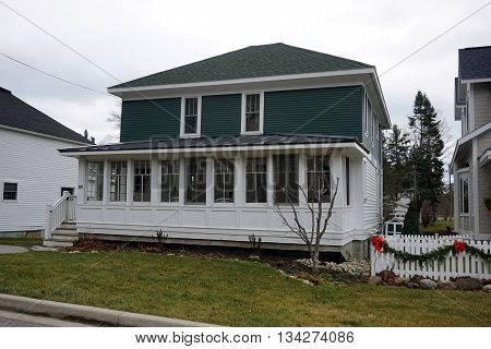 HARBOR SPRINGS, MICHIGAN / UNITED STATES - DECEMBER 24, 2015: A home with an enclosed front porch on Fourth Street n Harbor Springs.