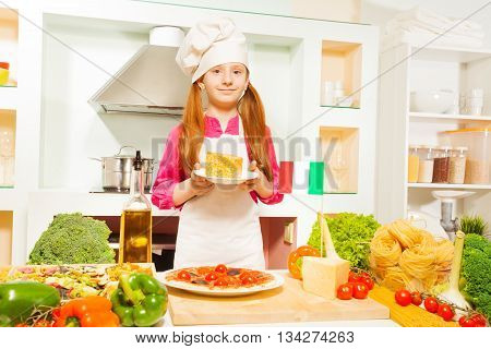 Pretty Italian girl in cook's hat and apron, holding plate with cheese in the kitchen