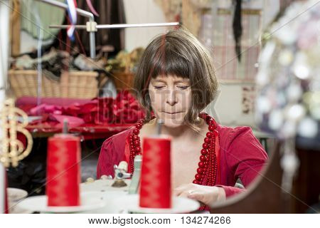A seamstress in red working with a sewing machine