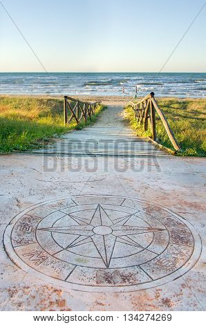 Foggia Italy August 17 2014: A big wind rose symbol before the walkway that lead to the beach