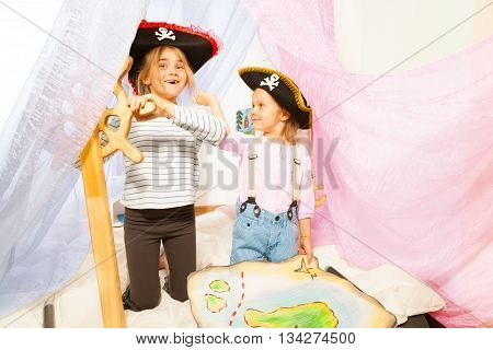 Two funny girls in pirate's three-corned hats, steering the ship with toy wooden helm