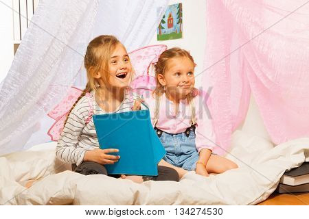 Two little smiling girls with pink wings  reading a book at the bed with net valance