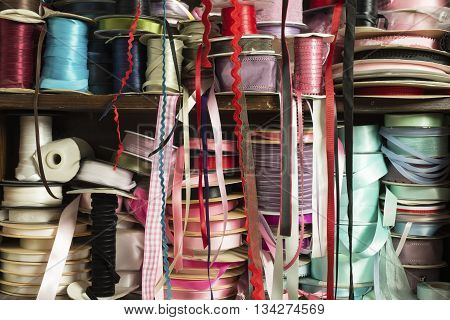 Rolls of satin ribbon tailoring supplies of different colors on wodden shelving