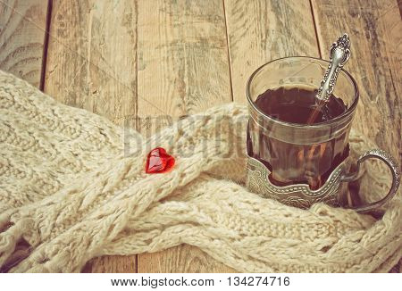 cup of hot tea in cup holder warm scarf red heart on wooden table vintage style