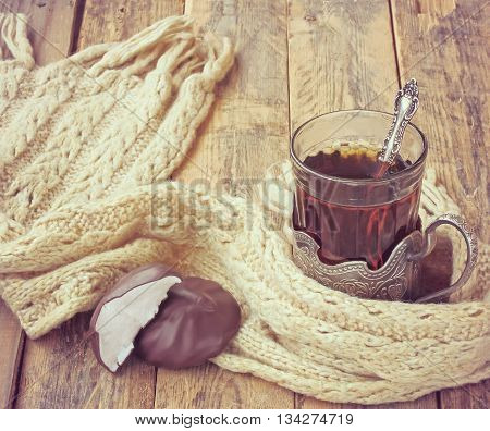 cup of tea in cupholder zephyr in chocolate warm scarf on wooden table vintage style