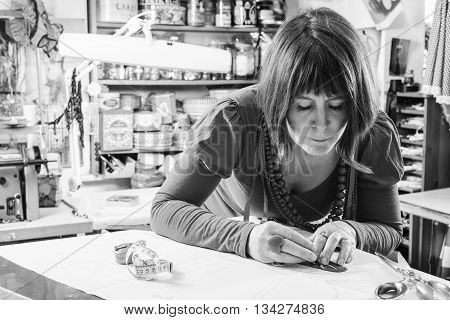 Grayscale image of seamstress measuring and tracing paper