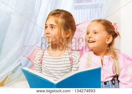 Two little girls, beautiful pixies with pink wings, reading fairy-tale before bedtime