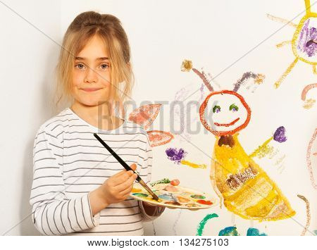 Young painter, seven years old girl, mixing colors at the pallet for her drawing