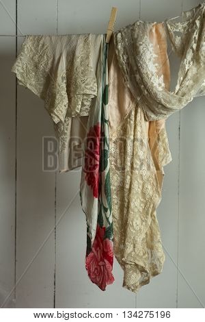 An off-white lace fabric and a floral design cloth pinned to a clothesline on a white wooden panel background.