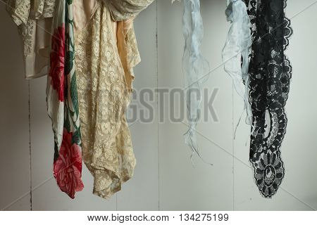 An assortment of dangling lace fabric on a white wooden panel background.
