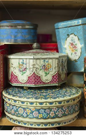 A collection of vintage decorative tin canisters of different shapes and sizes on a wooden shelf