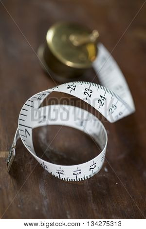 Measuring tape slightly unrolled on a dark wooden surface.
