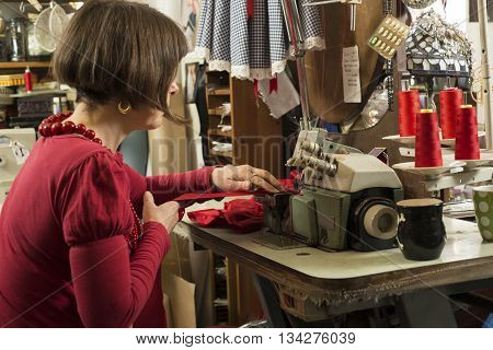 A seamstress in red seated by and working on a sewing machine stitching pieces of red cloth