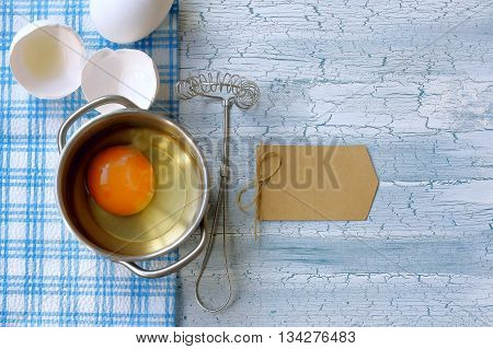 broken raw egg in pan whisk for whipping paper label on wooden table