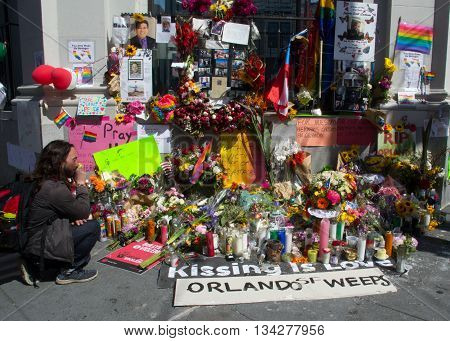 San Francisco, CA 6/13/16 Man pays respects at an impromptu memorial on Castro Street in San Francisco to the shooting victims in Orlando, FL.