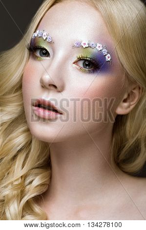 Beautiful young blonde woman with creative make-up color curls and flowers on eyebrows. Beauty face. Art makeup. Photos shot in studio