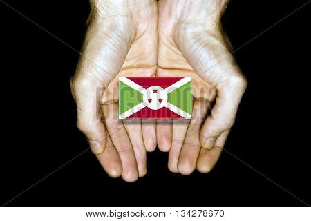 Flag of Burundi in hands isolated on black background.