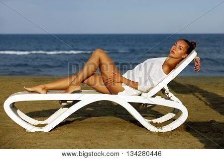 Beautiful girl on a deckchair on the coastline