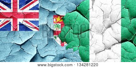 Fiji flag with Nigeria flag on a grunge cracked wall