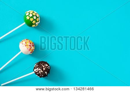 Sweet colorful cake pops on blue background