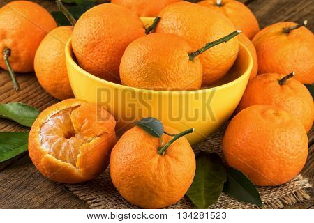 Tangerines in yellow bowl. Fresh tangerines on rustic background.