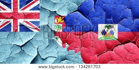 Fiji flag with Haiti flag on a grunge cracked wall