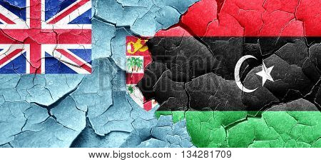 Fiji flag with Libya flag on a grunge cracked wall