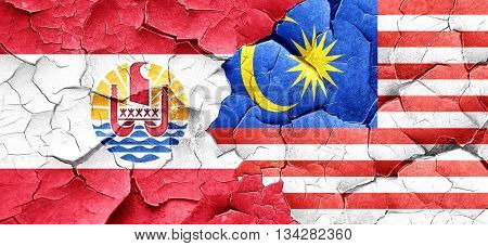 french polynesia flag with Malaysia flag on a grunge cracked wal