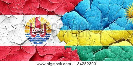 french polynesia flag with rwanda flag on a grunge cracked wall