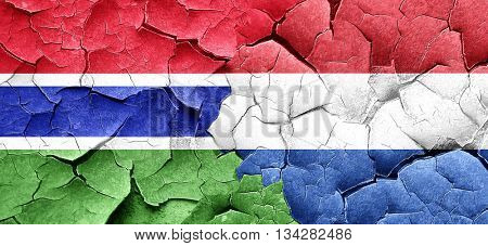 Gambia flag with Netherlands flag on a grunge cracked wall