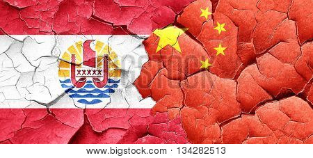 french polynesia flag with China flag on a grunge cracked wall