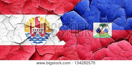 french polynesia flag with Haiti flag on a grunge cracked wall