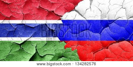 Gambia flag with Russia flag on a grunge cracked wall