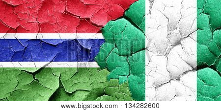 Gambia flag with Nigeria flag on a grunge cracked wall