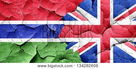 Gambia flag with Great Britain flag on a grunge cracked wall