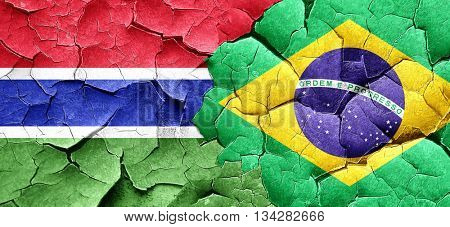 Gambia flag with Brazil flag on a grunge cracked wall