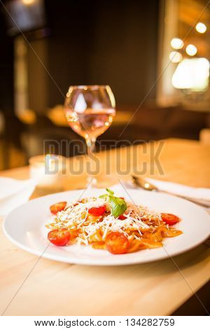 farfalle with tomatoes,cheese and fresh green basil in restaurant