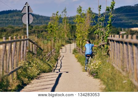 Woman On Bicycle Resting At Fence. Old Train Cycling Path. Bicis Verdes. Mallorca. Spain.