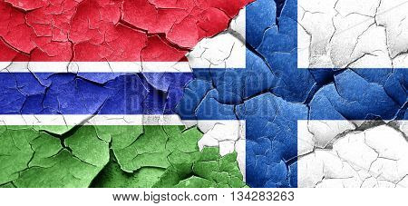 Gambia flag with Finland flag on a grunge cracked wall